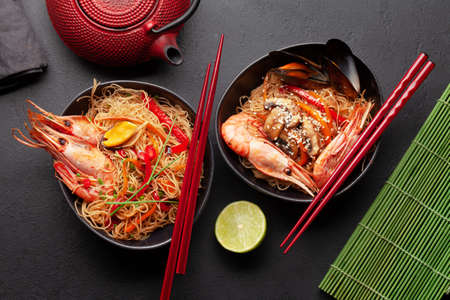 Wok with stir fried noodles, shrimps and vegetables on stone background. Top view flat lay