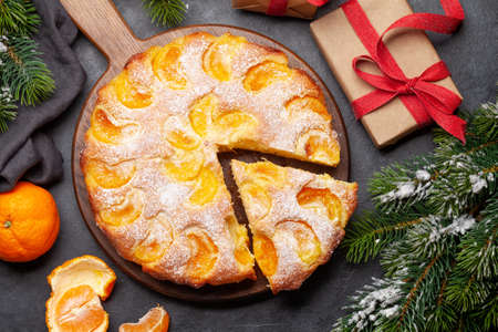 Citrus dessert holiday cake, tangerines and christmas gift boxes. Top view flat lay Standard-Bild