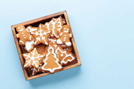 Christmas card with gingerbread cookies over blue background. Top view flat lay with space for xmas greetings Standard-Bild