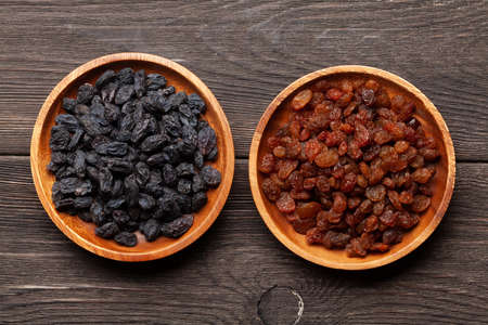 Various dried fruits in bowls on a wooden table. Top view flat lay Standard-Bild