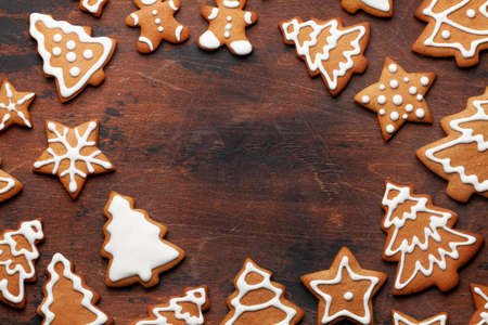 Christmas card with gingerbread cookies over wooden background. Top view flat lay with space for xmas greetings