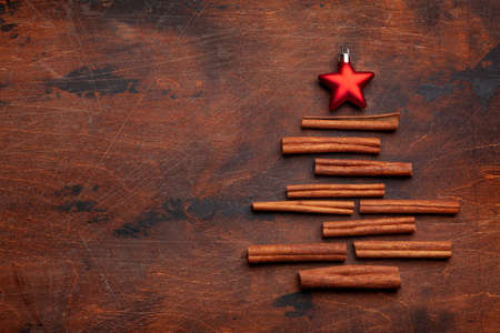 Christmas card with fir tree shaped cinnamon spice and star decor over wooden background. Top view flat lay with space for xmas greetings