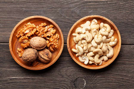 Various nuts in bowls on a wooden table. Top view flat lay