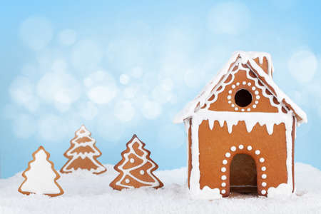 Christmas greeting card with gingerbread house, gingerbread fir trees in snow and copy space Standard-Bild