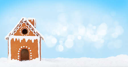 Christmas greeting card with gingerbread house in snow and copy space Standard-Bild
