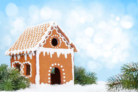 Christmas greeting card with gingerbread house, fir tree in snow and copy space