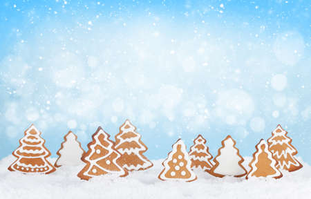 Christmas greeting card with homemade gingerbread trees in snow. With copy space for your greetings