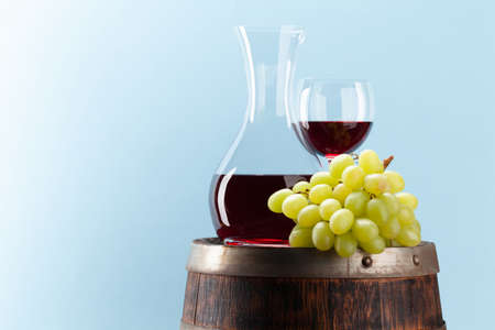 Decanter with red wine on old wooden barrel in front of blue background with copy space