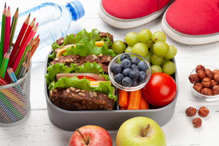 Healthy lunch box with sandwich and fresh vegetables, water bottle, nuts and fruits on wooden table