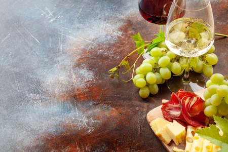 White and red wine glasses, grape and appetizer board with cheese and prosciutto. With copy space Standard-Bild