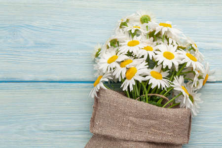 Garden camomile flowers bouquet on blue wooden table. Top view flat lay with copy space