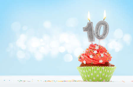 Birthday cupcake with number ten burning candle over blue background with copy space for your greetings