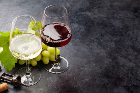 White and red wine glasses and white grape on stone table with copy space Standard-Bild