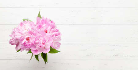 Beautiful garden peony flowers bouquet on wooden background. Top view flat lay with space for your holiday greetings