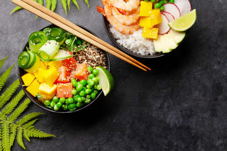 Poke bowls with shrimps, salmon, avocado and mango. Traditional hawaiian meal. Top view flat lay with copy space