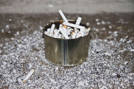 ashtray overflowed with stubs and ashes round it photo