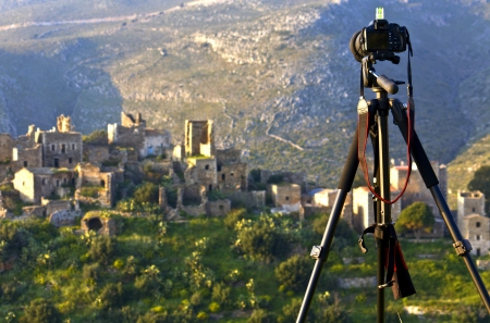 Camera on a tripod ready to shoot a landscape scenery at Mani, Greece photo
