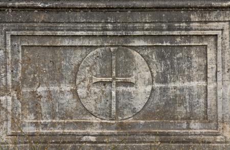 symbolism: Old christian plaque with a cross relief on it Stock Photo