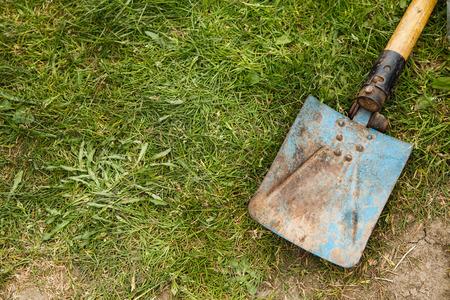 Blue rusty spade on grass Stock Photo