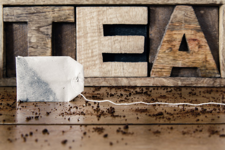 teabag: Teabag in front of wooden lettering