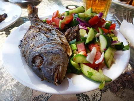 green and purple vegetables: delicious fried fish on a white plate with salad of a vegetables green cucumber, red tomato, purple cabbage macro