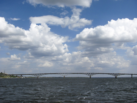 bridging: White cumulus clouds in the blue sky above the bridge between the cities of Saratov and Engels through the river Volga