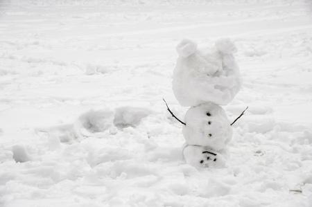 cabeza abajo: El muñeco de nieve creativo es al revés en la nieve en el invierno