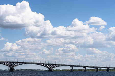 bridging: Impressive landscape of the beautiful white clouds in the blue sky above the bridge between the cities of Saratov and Engels through the river Volga