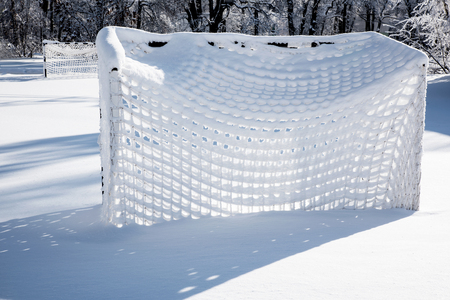Football goal covered with snow in winter frosty day