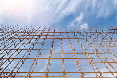 Steel reinforcement bar and timber form works at construction site on blue summer sky background