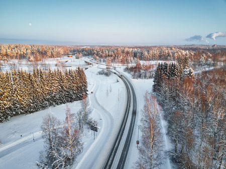The road passes on the outskirts of the Finnish city of Joensuu, winter, a lot of snow, in the blue sky the moon