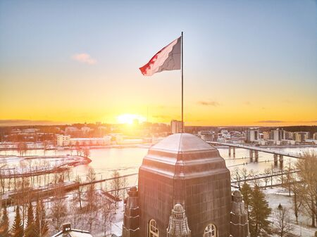 Aerial view of flag of North Karelia. Flag on the spire of City Hall. Joensuu, Finland in the morning in the first frost. In the background is the park and the Pielisjoki River. Bridge over the river.