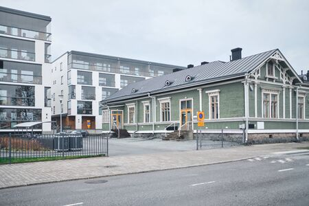 The old wooden building and the brand new modern apartment building in Joensuu, Finland. Retro and modern.