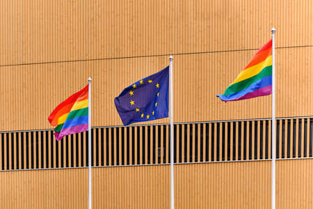 The Pride flags and European Union flag on white flagpoles against the wooden wall in Finland