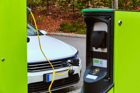 The modern electric car charged on the car parking in National Park in Finland.