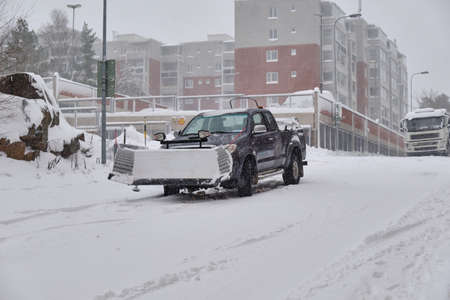 Pickup snowplow on the snow-covered street during a snow storm in Finland