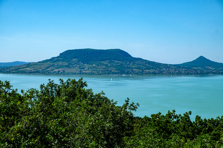 sailboat on water, greenery in foreground fameus Badacsony hill in background - summertime and vacation at Balaton lake Standard-Bild