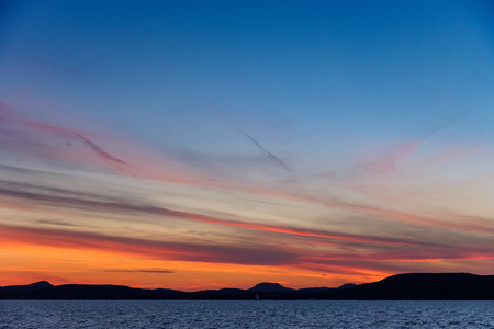colorful sunset at Balaton lake in summer - thin clouds, dark water and mountains in background Imagens