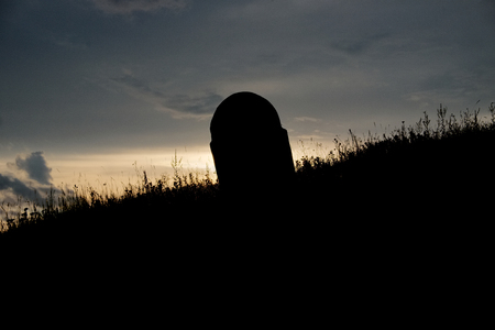 silhouette of lonely graveyard stone on hill at sunset