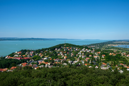 small town in foreground, the blue and green lake in background - summertime and vacation at Balaton Stock Photo