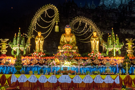 The celebration of the Buddha day, Vesak - Vesakha - Waisak at Borobudur, Indonesia, 2017, Altar with golden colored buddha-statue and offerings, ancient stupa in background, night