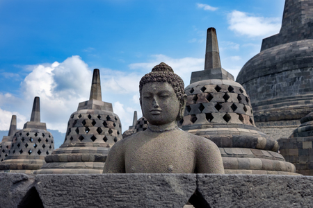 Borobodur ancient heritage of buddhism, Buddha statue and bell-shaped stupas on the main stupa of Borobudur, with blue cloudy sky / Borobodur ancient heritage of buddhism Banque d'images