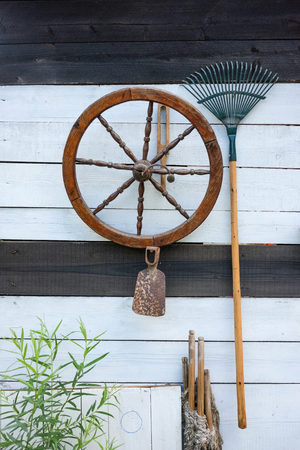 tools of rural life, old wooden wheel, rusty hoe, rake hanging on black and wihte painted wppden wall