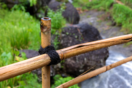 cracked bamboo bridge railing over a tropical river, close up