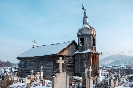 Abandoned Moldovan wooden church surrounded gravestones - winter Imagens