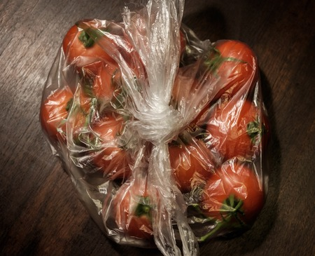 tomatoes in transparent plastic bag on brown wooden surface, above, dark tones - close up