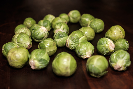 raw green brussels sprouts on brown wooden surface - close up Imagens