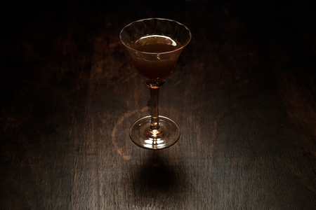 glass of drink - crystal cup on dark aged wooden desk