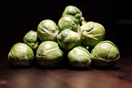 raw green brussels sprouts heap on brown wooden surface - spot light - close up - untouched