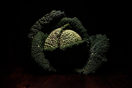 kale head, opened leaves on brown wooden desk - close up - dark tones, deep shadows